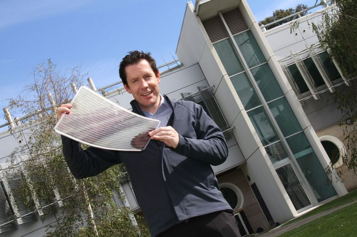 Scott Watkins holding a sheet of flexible solar cells. Courtesy CSIRO.